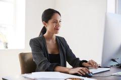 使用计算机的年轻亚裔妇女,微笑在办公室 免版税图库摄影