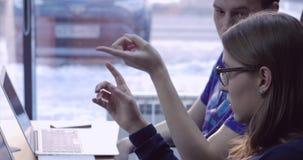 使用计算机的年轻商人在办公室 在一个创新产品的两个装饰员的同事 股票视频