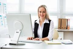 使用计算机的年轻女商人在办公室 免版税图库摄影