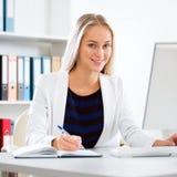使用计算机的年轻女商人在办公室 库存图片