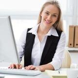 使用计算机的年轻女商人在办公室 库存照片