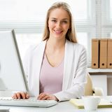 使用计算机的年轻女商人在办公室 图库摄影