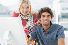 使用计算机的微笑的偶然夫妇在明亮的办公室 免版税库存图片