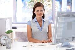 使用计算机的微笑的办公室工作者 免版税库存照片