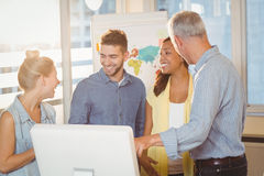 使用计算机的微笑的商人在会议室 免版税库存图片
