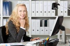使用计算机的微笑的女实业家在书桌 免版税库存照片