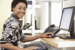 使用计算机的微笑的女实业家在办公室 库存照片