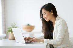 使用计算机的微笑的年轻亚裔女实业家在网上运转 免版税库存图片