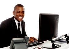 使用计算机的微笑的新总公司人 免版税库存图片