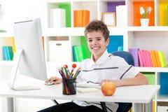 使用计算机的微笑的男孩 免版税库存图片