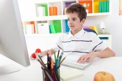 使用计算机的微笑的男孩 免版税图库摄影