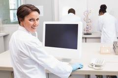 使用计算机的微笑的科学家,当同事工作时 免版税库存照片