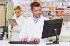 使用计算机的微笑的药剂师 图库摄影