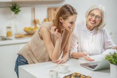 使用计算机的快乐的家庭在厨房里 免版税图库摄影