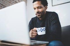 使用计算机的快乐的非洲人和微笑,当坐沙发时 拿着陶瓷杯子的黑人手中 概念 库存图片