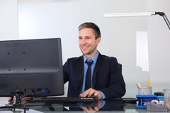 使用计算机的愉快的商人在他的办公室 免版税库存照片