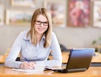 使用计算机的愉快的女孩在图书馆。 免版税库存图片