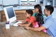 使用计算机的愉快的家庭在厨房里 图库摄影