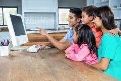 使用计算机的愉快的家庭在厨房里 免版税库存照片