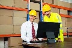 使用计算机的愉快的仓库工作者和经理 免版税库存照片