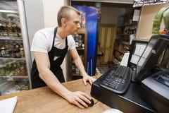 使用计算机的推销员画象在现金柜台在超级市场 免版税库存照片