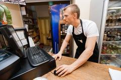 使用计算机的推销员画象在现金柜台在超级市场 库存图片