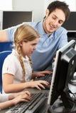 使用计算机的教师帮助的女孩在选件类 库存照片