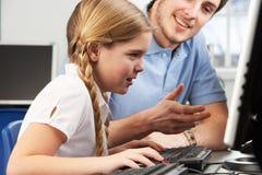 使用计算机的教师帮助的女孩在选件类 图库摄影