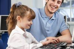 使用计算机的教师帮助的女孩在选件类 免版税库存图片