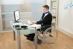 使用计算机的残疾商人 库存照片