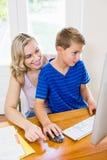 使用计算机的母亲和儿子在客厅 图库摄影