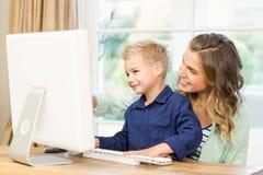 使用计算机的母亲和儿子 免版税图库摄影