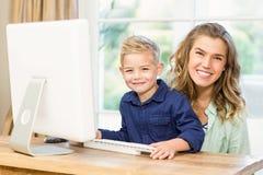 使用计算机的母亲和儿子 免版税库存图片
