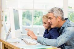使用计算机的父亲和儿子 免版税库存照片