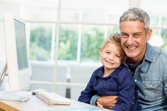 使用计算机的父亲和儿子 免版税图库摄影