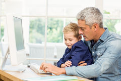 使用计算机的父亲和儿子 免版税库存图片