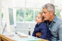 使用计算机的父亲和儿子 库存照片