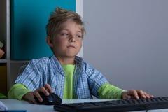 使用计算机的男孩在晚上 图库摄影