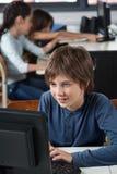 使用计算机的男小学生在书桌 免版税库存照片