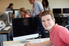 使用计算机的男性大学生在教室 库存照片