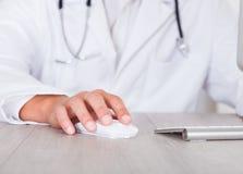使用计算机的男性医生的手 免版税库存图片