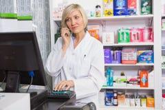 使用计算机的白肤金发的药剂师,当打电话时 免版税图库摄影