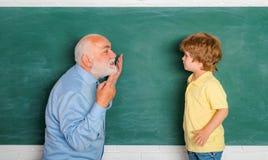 使用计算机的老师和男小学生在黑板的类 祖父和孙子画象,当工作时 免版税库存图片