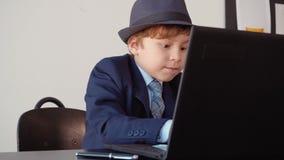使用计算机的聪明的小男孩年轻企业家 股票视频