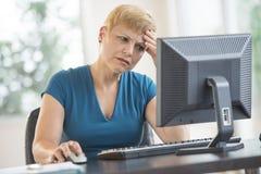 使用计算机的被拉紧的女实业家在书桌 库存图片