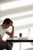 使用计算机的被注重的男性大学生在教室 库存图片
