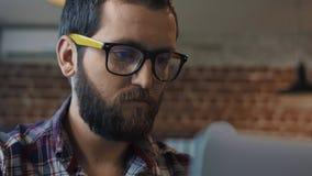 使用计算机的被聚焦的有胡子的人 免版税库存图片