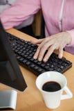 使用计算机的资深学生在书桌在教室 免版税库存图片