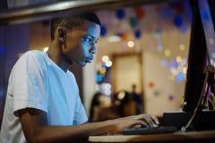 使用计算机的非裔美国人的男孩在晚上 免版税库存照片