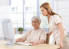 使用计算机的高级母亲和女儿 图库摄影